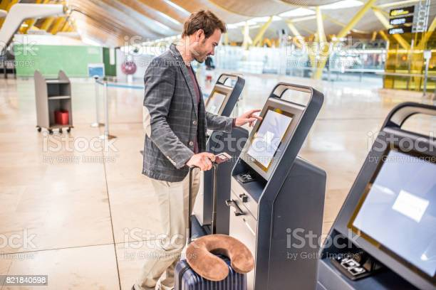 Happy Man Using The Checkin Machine At The Airport Getting The Boarding Pass Stock Photo - Download Image Now