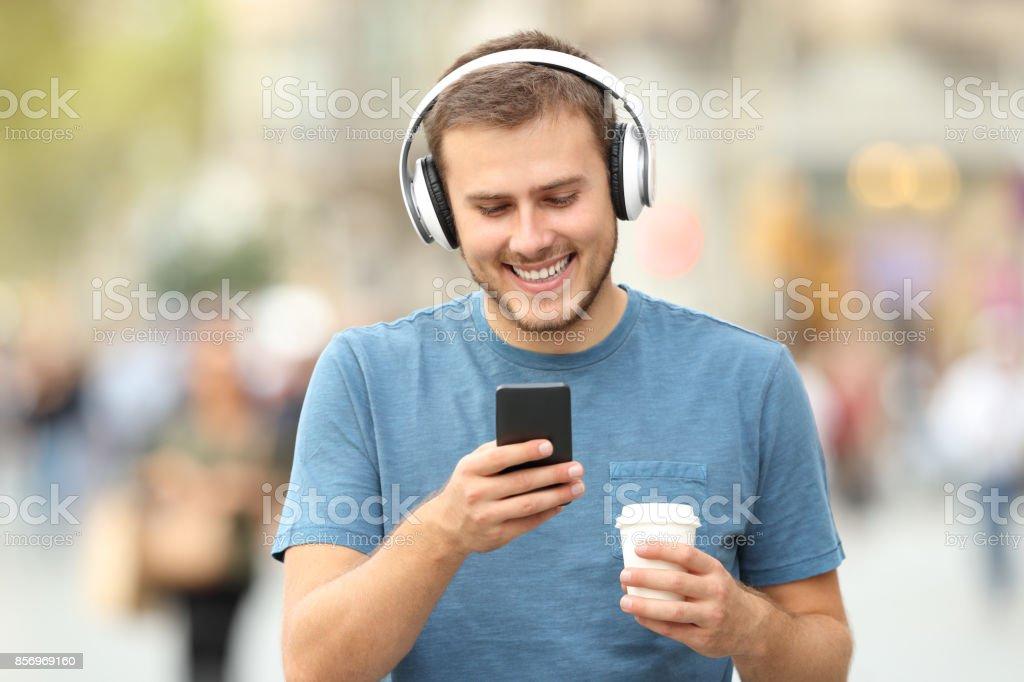 Happy man walking listening to music stock photo