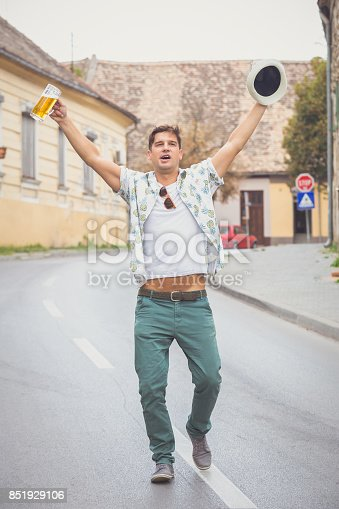 istock Happy man walking on the street and holding beer mug and hat 851929106