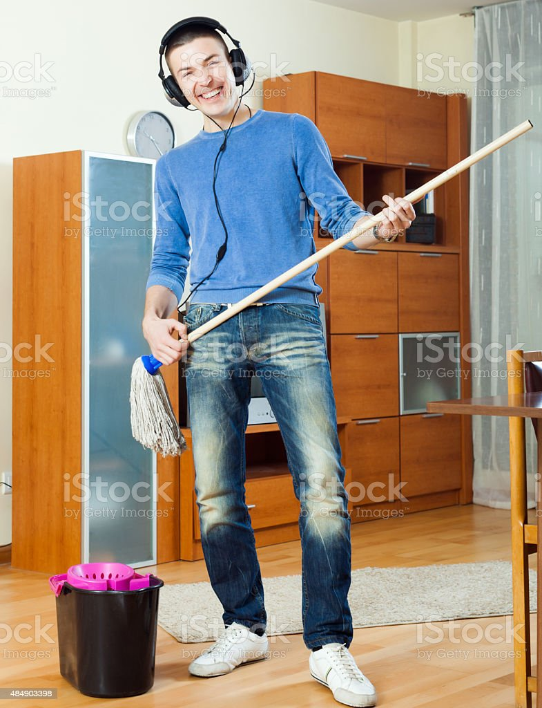 Happy man washing parquet floor with mop in living room stock photo