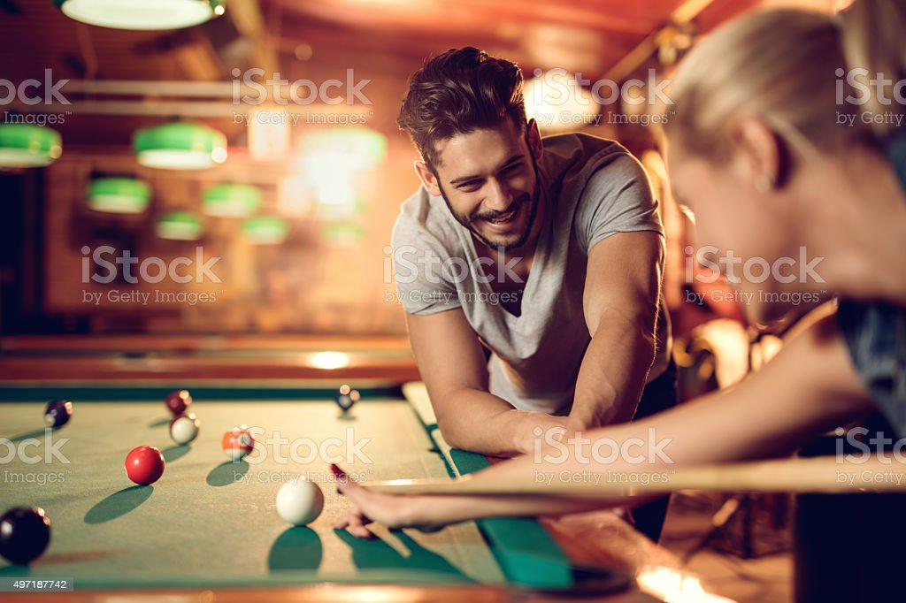 Happy man watching his girlfriend playing snooker in pool hall. stock photo