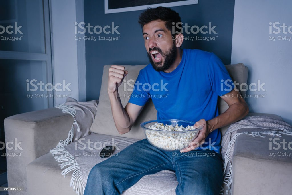 Happy man watching TV and cheering at night