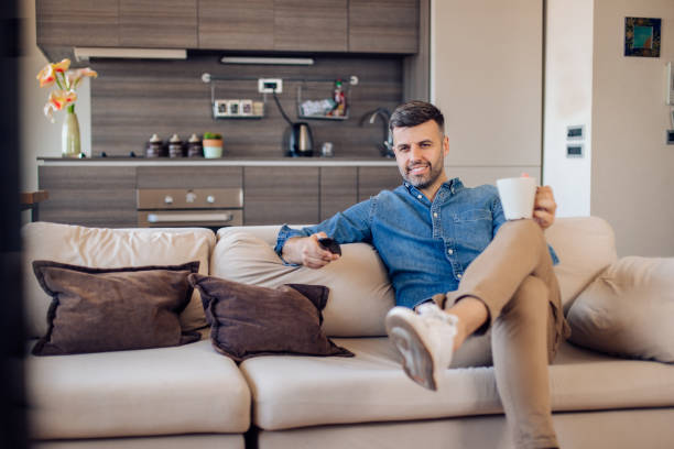 Happy man watching TV and drinking coffee stock photo