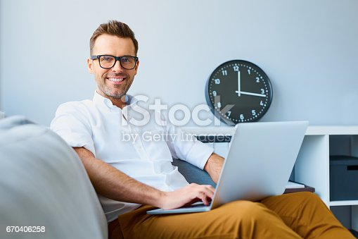 Happy man wearing glasses sitting with laptop relaxed  on sofa