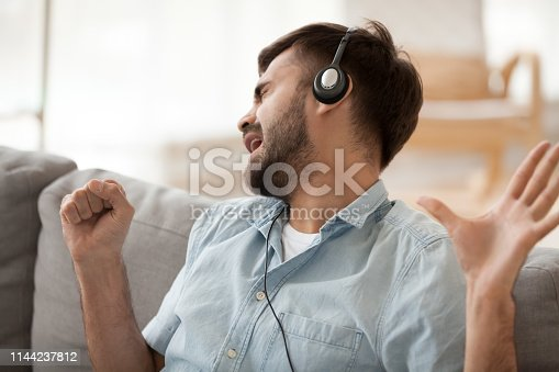Happy man wearing headphones singing song, imagine microphone in hand, funny guy sitting on cozy sofa in living room, listening to popular track, favorite music, having fun alone, moving in rhythm