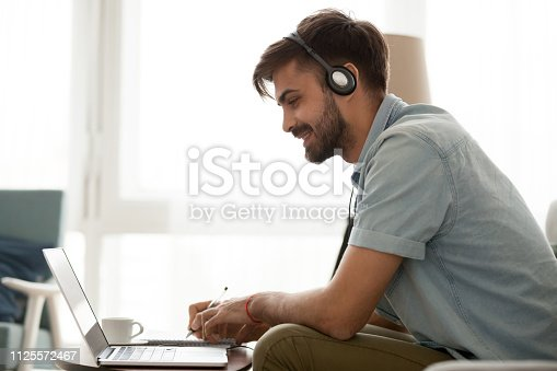 Happy man wearing headset study online learning foreign english language or watch webinar make notes, smiling male student in headphones looking at laptop elearning in internet write down information