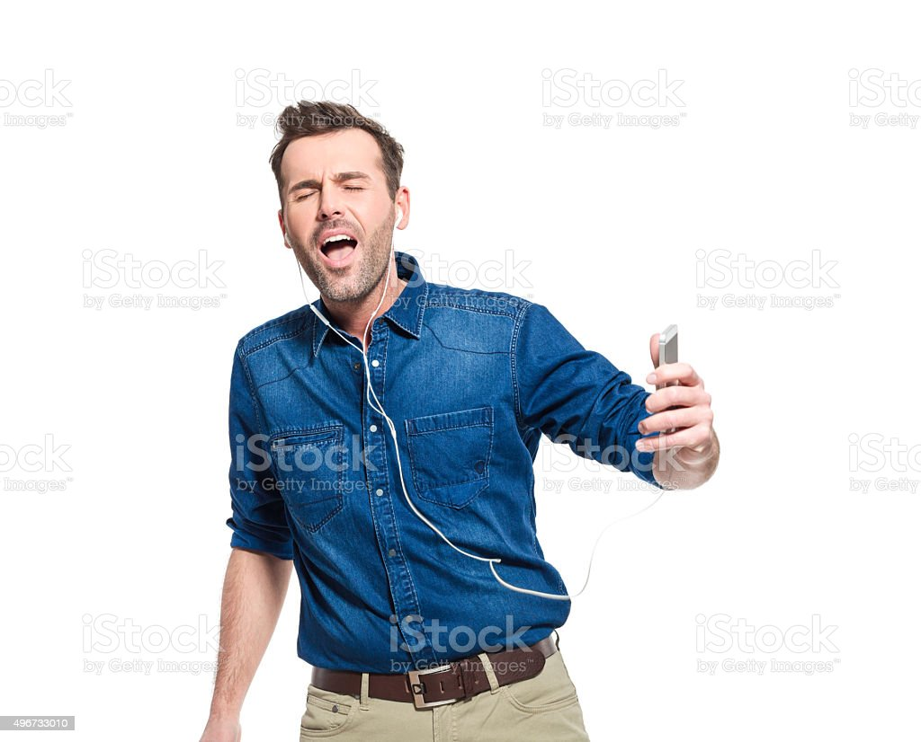 Happy man wearing jeans shirt, listening to music on phone Portrait of happy adult man wearing jeans shirt and earphone, listening to music on smart phone, singing with closed eyes. Studio shot, white background. 2015 Stock Photo