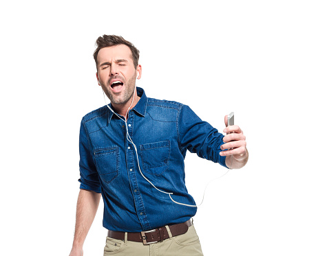Happy Man Wearing Jeans Shirt Listening To Music On Phone Stock Photo - Download Image Now