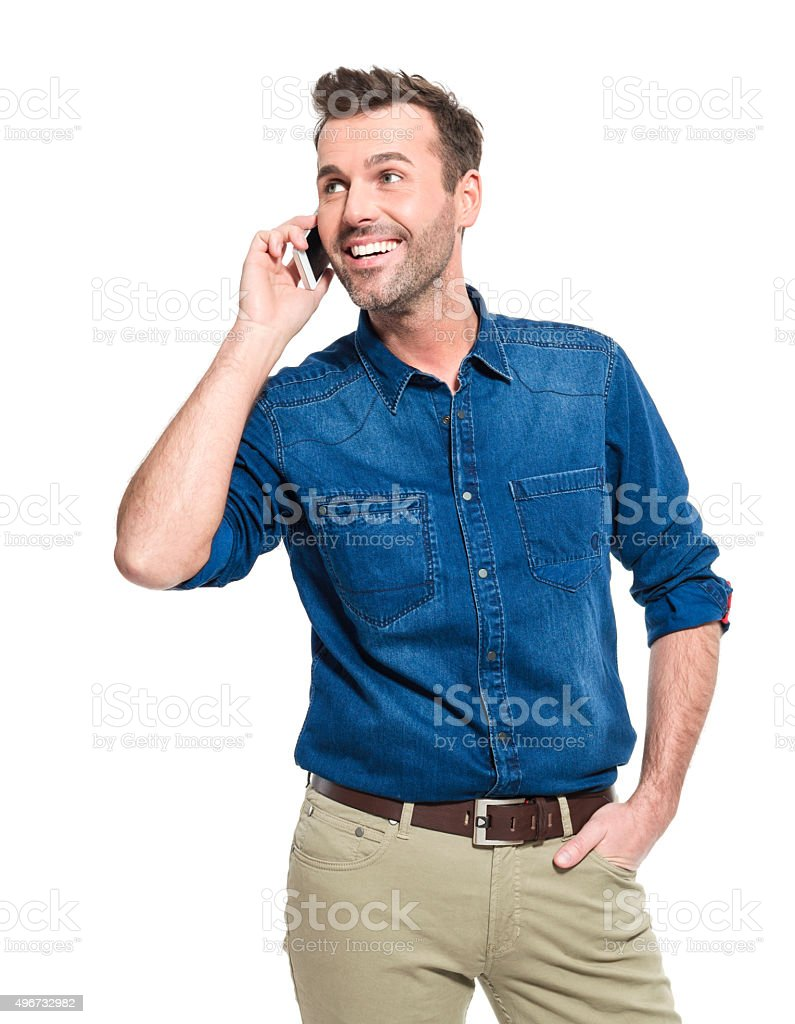 Happy man wearing jeans shirt, talking on cell phone Portrait of happy adult man wearing jeans shirt, standing against the white background and talking on mobile phone. 2015 Stock Photo