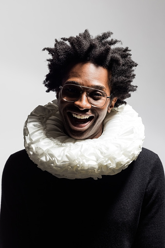 Excited afro american man wearing black turtleneck and white neck ruff, smiling at camera. Headshot on grey background.