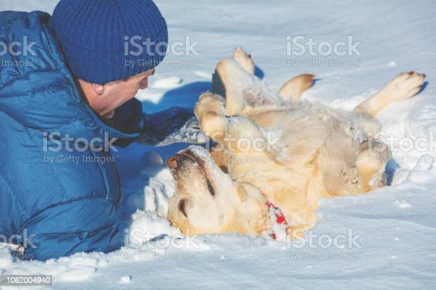 Happy man with a labrador retriever dog lying on the snow in winter picture id1062004940?b=1&k=6&m=1062004940&s=612x612&h=n30n h59boxwasbticgtdc kbhzfr 2e4ypeabd0mhe=