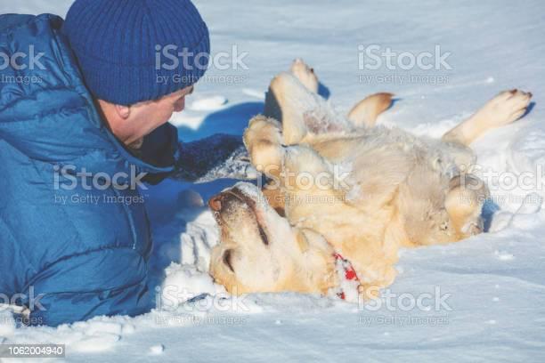 Happy man with a labrador retriever dog lying on the snow in winter picture id1062004940?b=1&k=6&m=1062004940&s=612x612&h=n30n h59boxwasbticgtdc kbhzfr 2e4ypeabd0mhe=