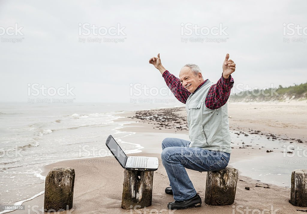 Happy man with a laptop on the beach royalty-free stock photo
