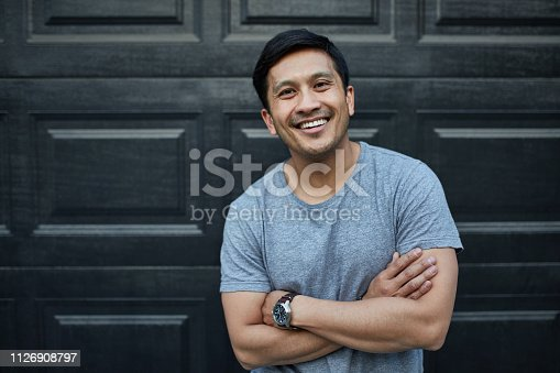 Portrait of smiling man with arms crossed. Happy mid adult male is standing against wall. He is in gray t-shirt at yard.