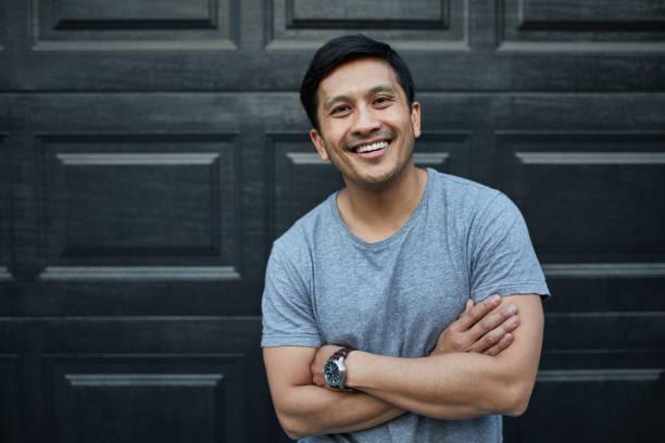 homem feliz com braços cruzados contra o muro no quintal - 35 39 anos - fotografias e filmes do acervo