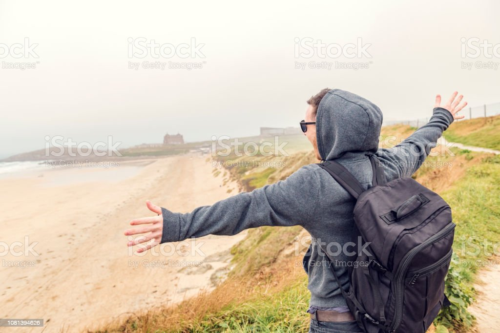Happy man with arms outstretched overlooking Fistral Beach, Newquay, Cornwall on an overcast Autumn day. stock photo