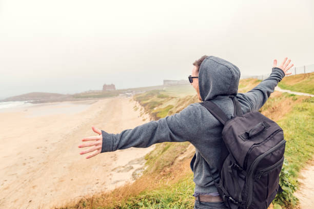 happy man with arms outstretched overlooking fistral beach, newquay, cornwall on an overcast autumn day. - cornwall stock photos and pictures