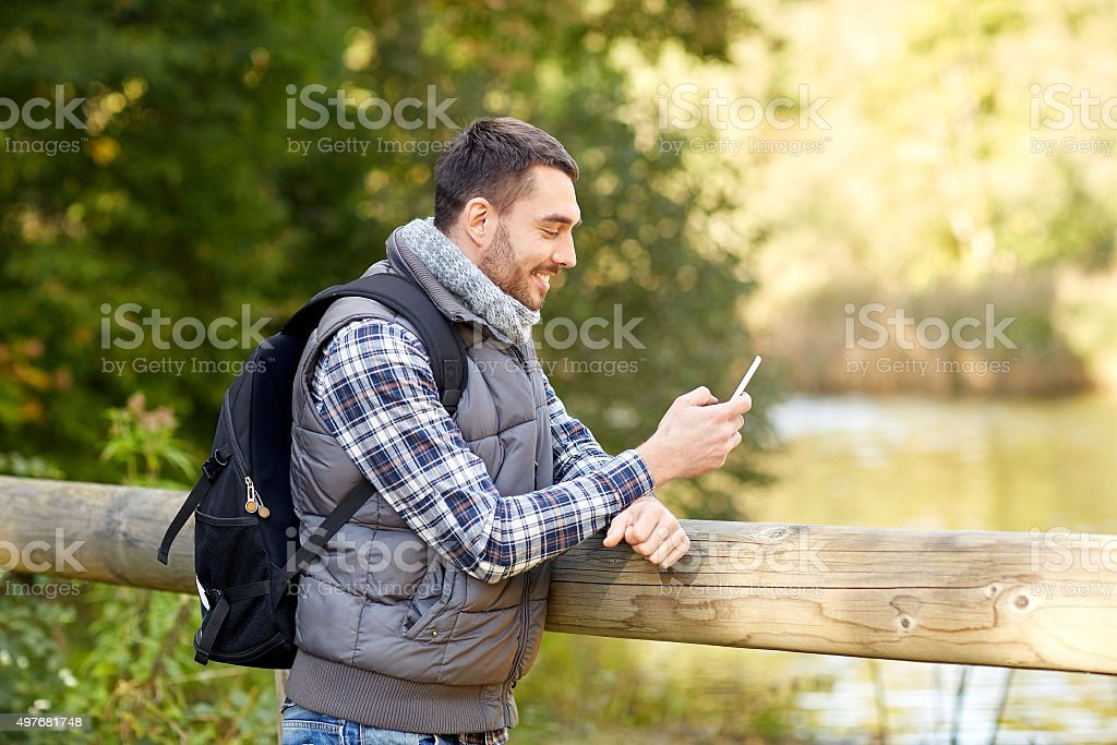 happy man with backpack and smartphone outdoors stock photo