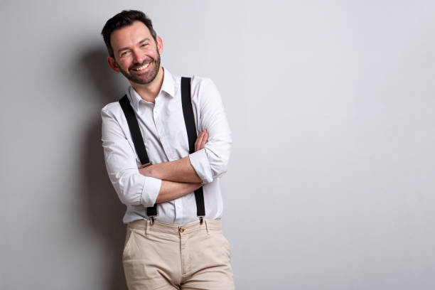 happy man with beard posing against gray wall Portrait of happy man with beard posing against gray wall suspenders stock pictures, royalty-free photos & images