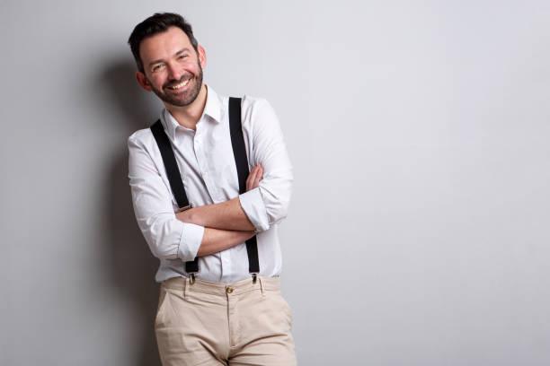 mutlu adam gri duvara poz sakallı - pantolon askısı stok fotoğraflar ve resimler