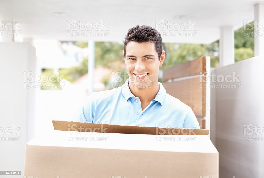 Happy man with box moving into new home smiling royalty-free stock photo