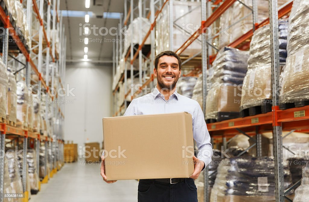 happy man with cardboard parcel box at warehouse stock photo