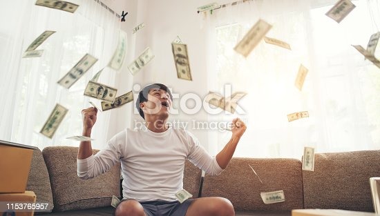 istock Happy man with cash dollars flying in home office, Rich from business online concept 1153765957