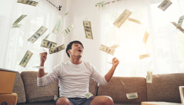 Happy man with cash dollars flying in home office, Rich from business online concept stock photo