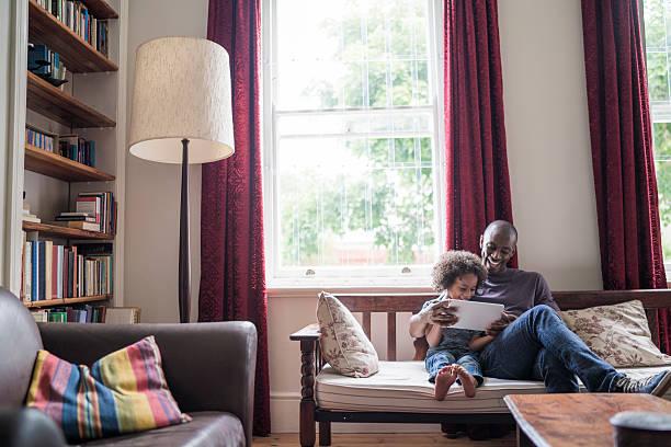 glücklicher mann mit tochter mit digitalen tablet auf couch - mädchenraum vorhänge stock-fotos und bilder