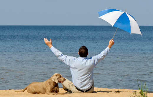 happy man with dog and umbrella on seacoast