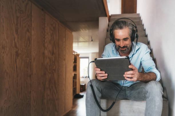 Glücklicher Mann mit Kopfhörer und Tablet auf Betontreppe – Foto
