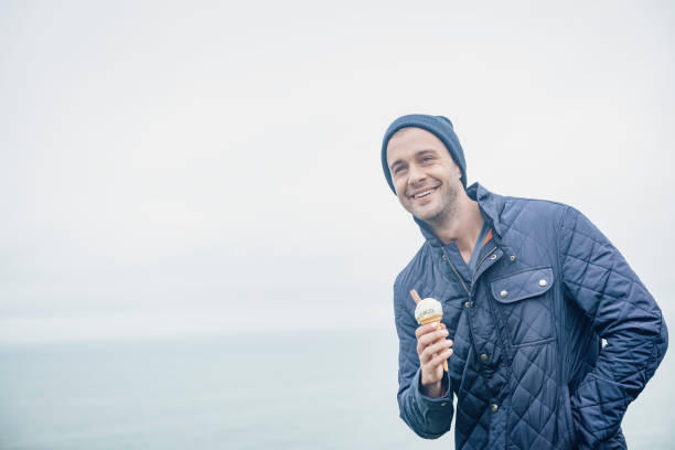 happy man with ice cream, autumn day, newquay, cornwall. - ice cream cone stock pictures, royalty-free photos & images