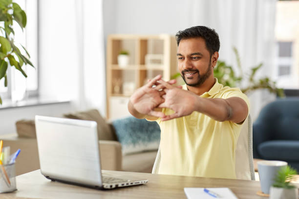happy man with laptop stretching at home office stock photo