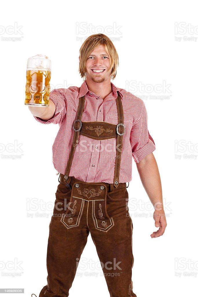Feliz hombre en pantalones de cuero (lederhose) tiene una tienda de cervezas del oktoberfest, stein - foto de stock