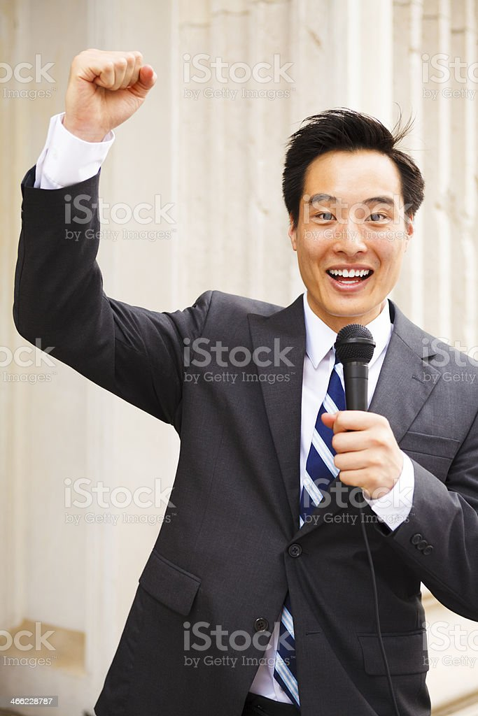 Happy Man with Microphone and Raised Fist royalty-free stock photo