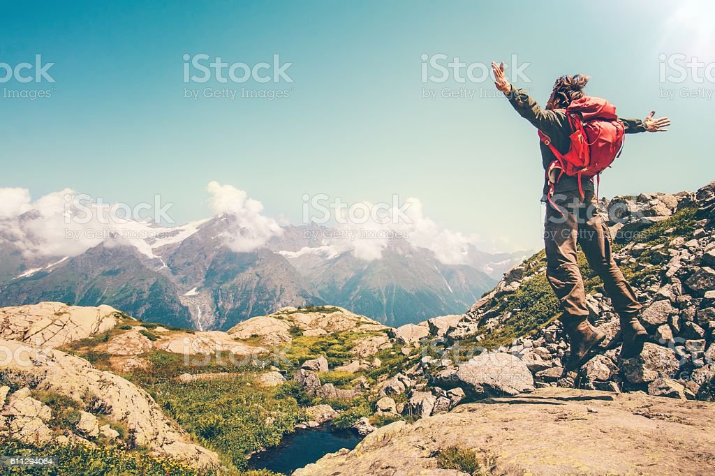 Happy Man with red backpack jumping hands raised mountains landscape – Foto