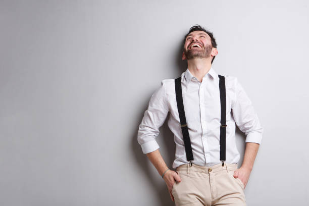 happy man with suspenders laughing and looking up Portrait of happy man with suspenders laughing and looking up suspenders stock pictures, royalty-free photos & images