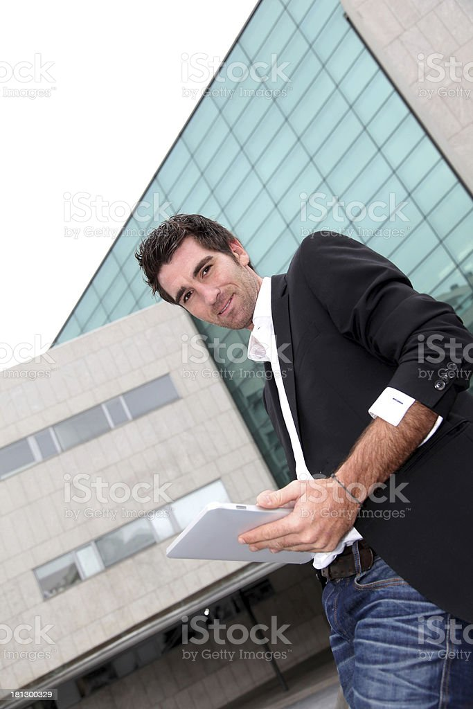 Happy man with tablet standing in front of modern building royalty-free stock photo