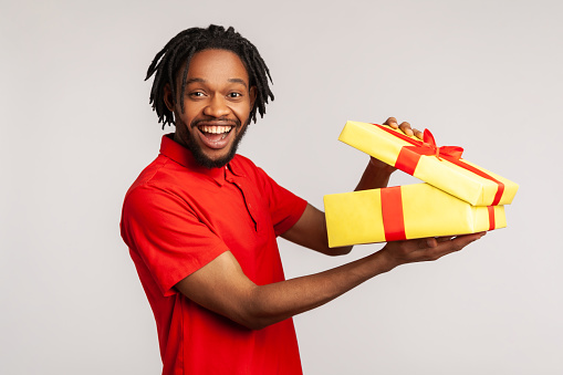 Happy man with toothy smile has dreadlocks wearing red casual style T-shirt, holding in hands unboxed gift, being satisfied with present. Indoor studio shot isolated on gray background.