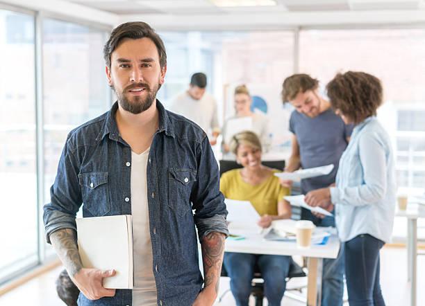 happy man working at a creative office - tattoo ideen stock-fotos und bilder