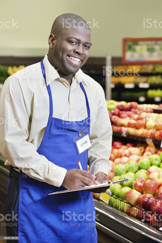 Happy man working in a supermarket produce department royalty-free stock photo