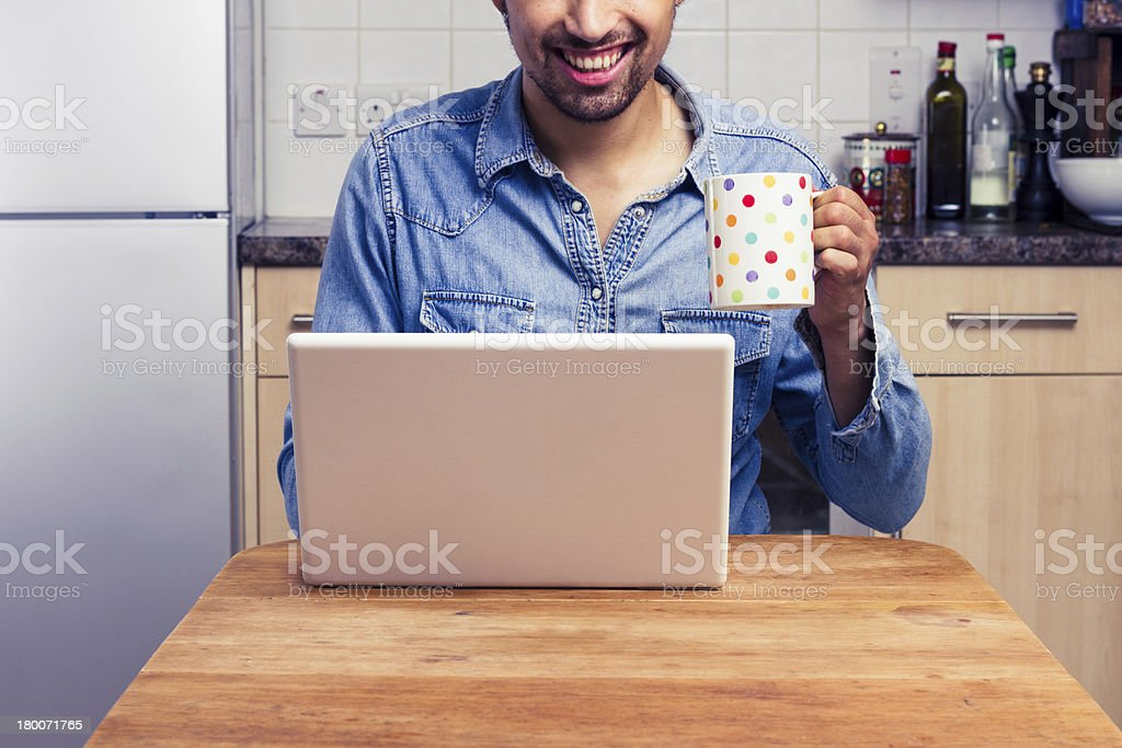 Happy man working on his laptop at home royalty-free stock photo