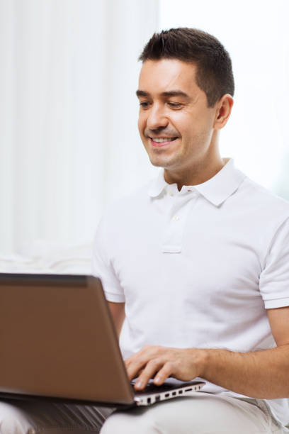happy man working with laptop computer at home stock photo