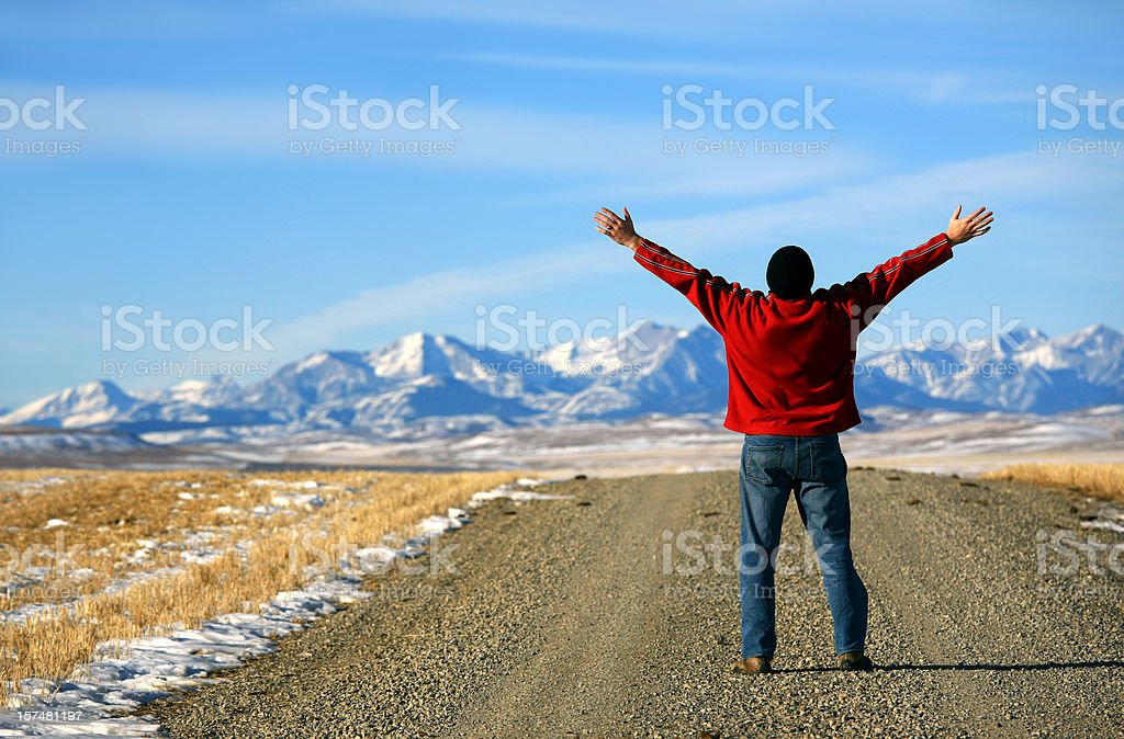 Happy Man Worshipping on Rural Road by Mountains royalty-free stock photo
