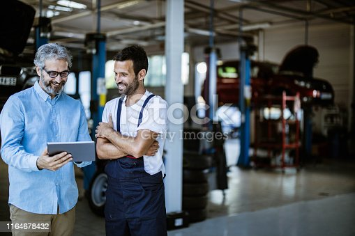 Mid adult manager and auto mechanic cooperating while reading plans on touchpad in a workshop.