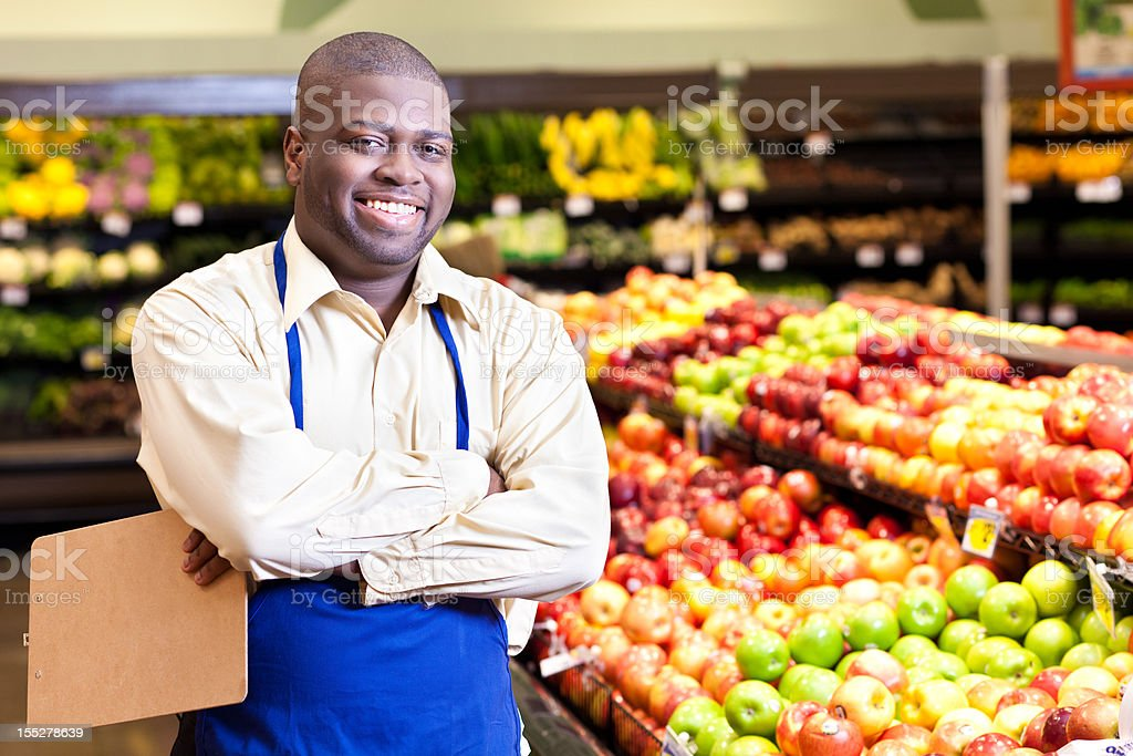 Happy manager at a grocery store produce area royalty-free stock photo