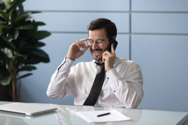 Happy manager holding pleasant call with partners. Happy manager sitting at desk, holding pleasant call with partners. Smiling employee talking on mobile phone, receiving good news. Laughing worker enjoying break, communicating with friends via phone. bingo caller stock pictures, royalty-free photos & images