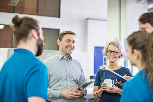 happy manager meeting with workers in printing factory - office worker stock photos and pictures