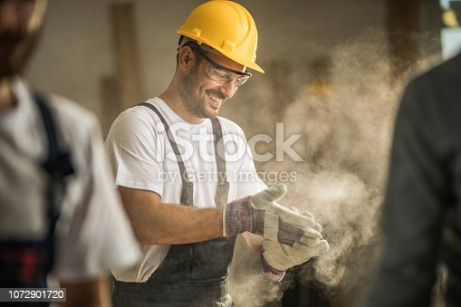 Young happy worker cleaning sawdust from his protective gloves at construction site.