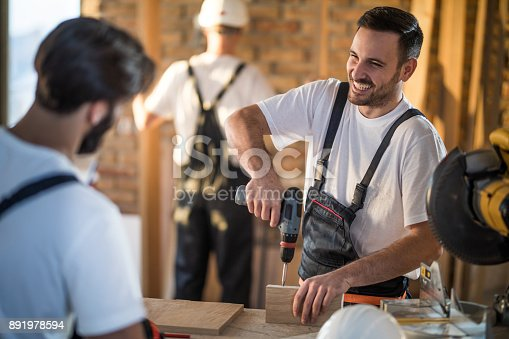 istock Happy manual worker talking to his colleague while working on home improvements. 891978594
